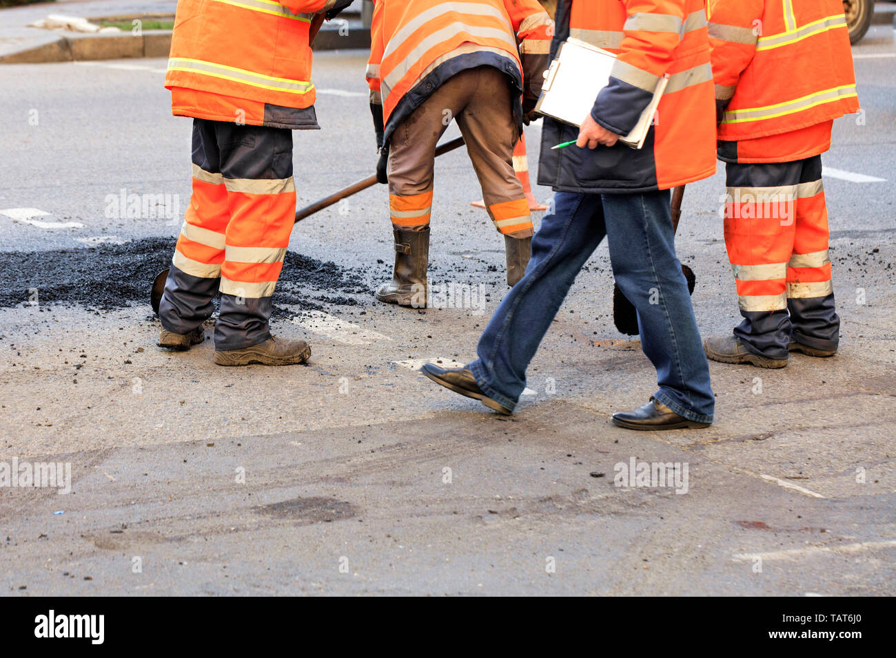 Team of road workers with shovels patch holes on the road with fresh asphalt in road construction. - Stock Image
