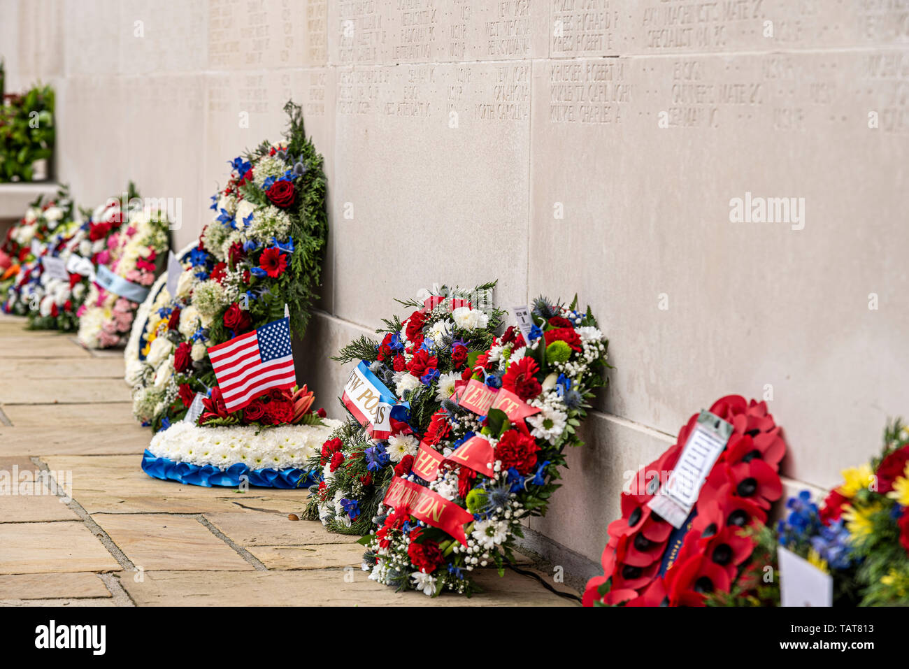 Wreaths against the Memorial Wall of the Missing on US Memorial Day remembrance event at Cambridge American Cemetery and Memorial, Cambridgeshire, UK. - Stock Image