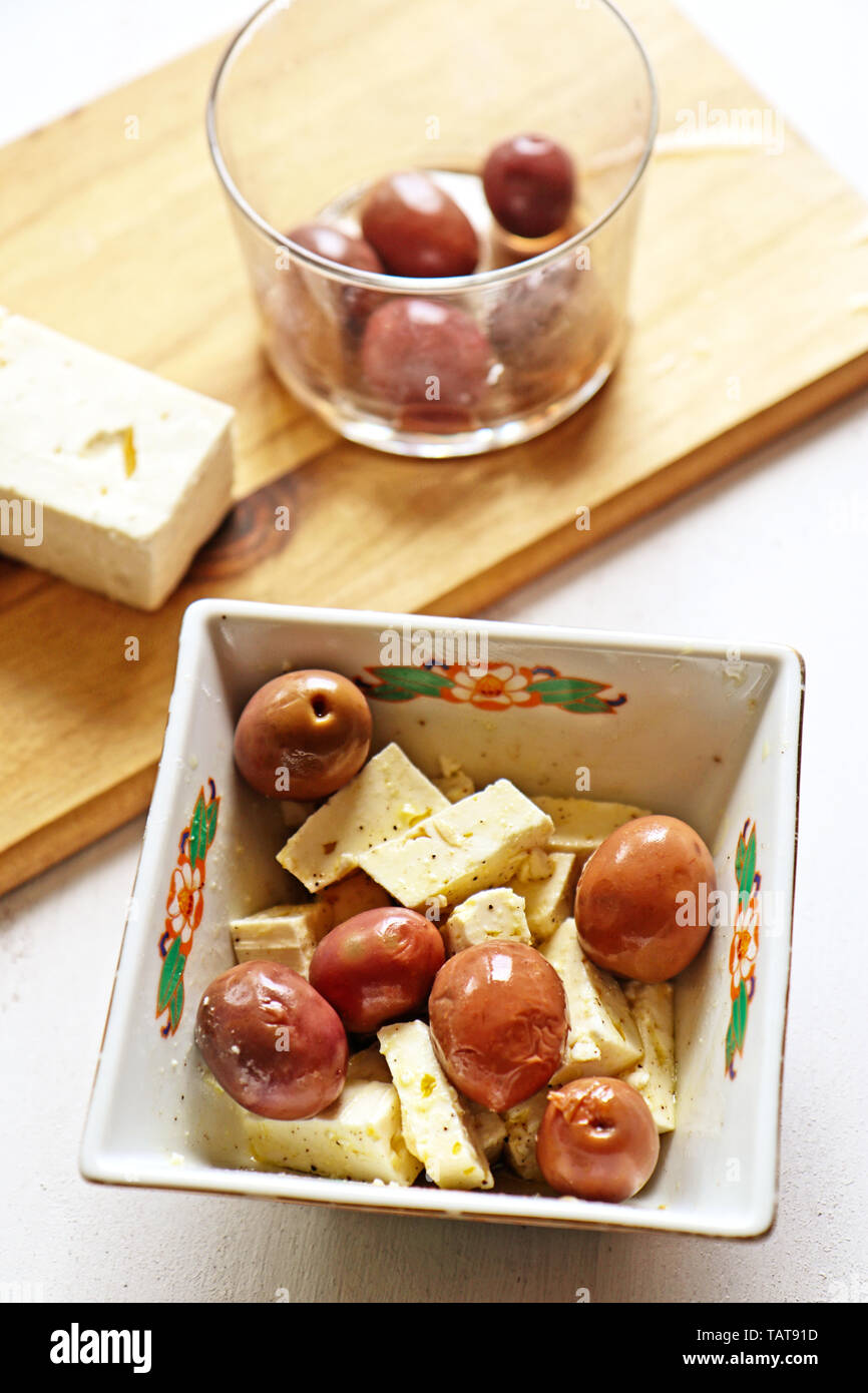 Feta cheese and Greek black olives dressed with pepper and olive oil Stock Photo