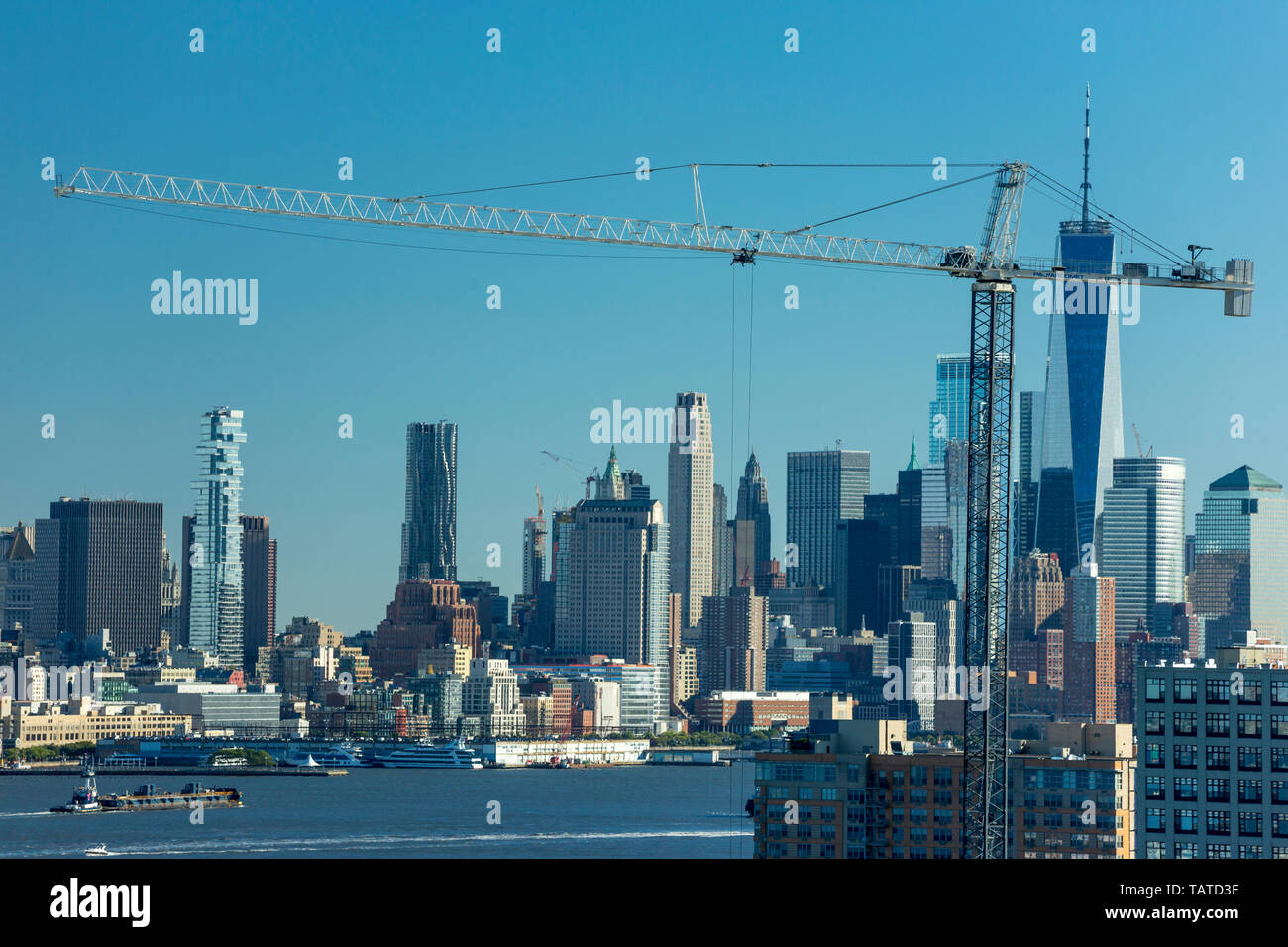 DOWNTOWN MANHATTAN SKYLINE HUDSON RIVER WITH CONSTRUCTION CRANES HOBOKEN NEW JERSEY USA Stock Photo