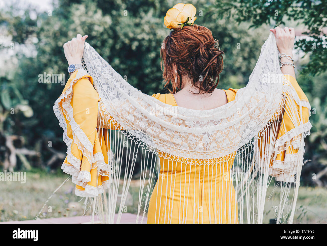 A back Spanish woman wearing a yellow traditional flamenco style dress standing with manila shawls with fringes - Stock Image