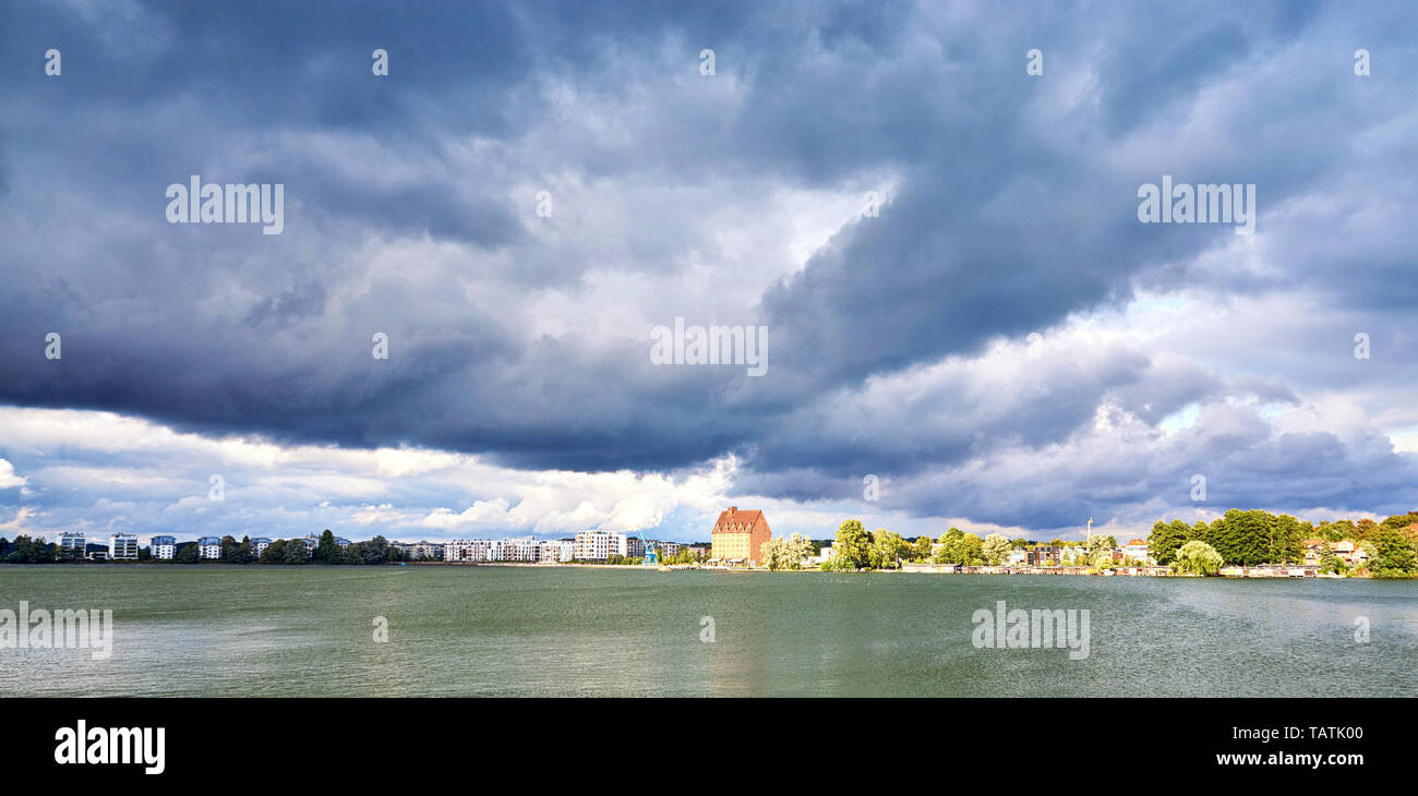 Old storage and development area at the Ziegelsee in Schwerin under dramatic clouds. Mecklenburg-Vorpommern, Germany Stock Photo