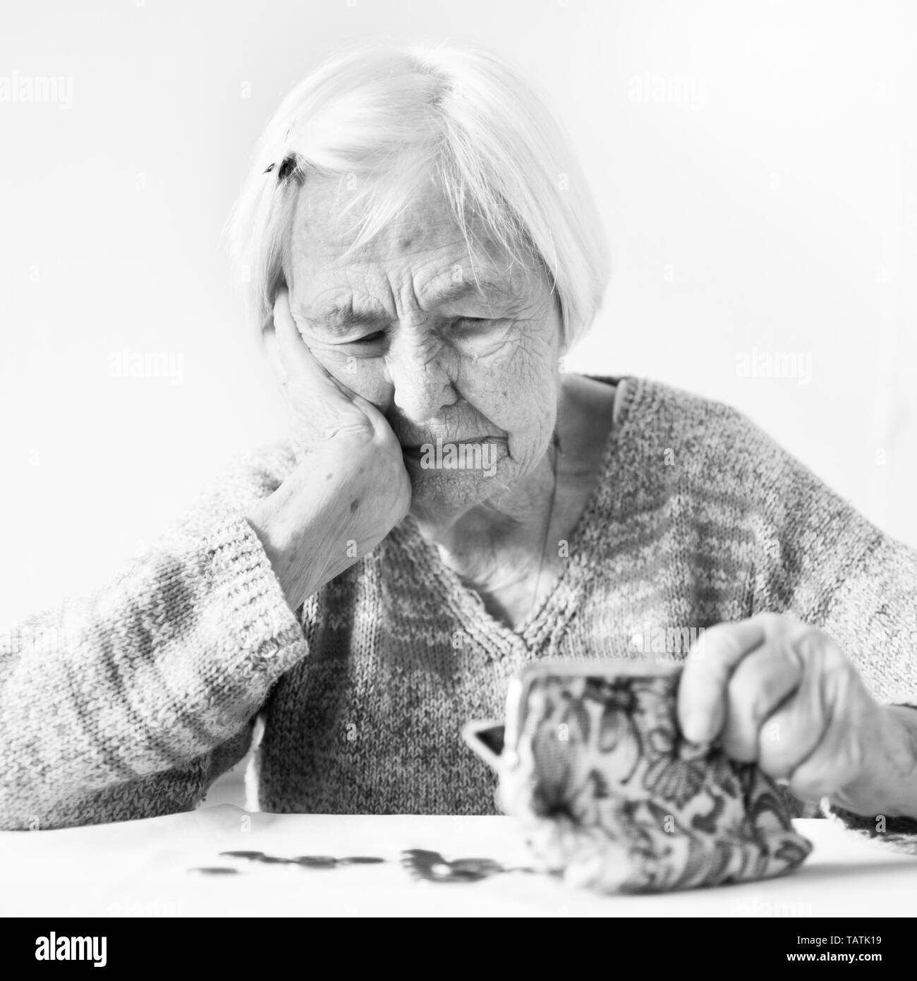 Concerned elderly 96 years old woman sitting at table at home and counting remaining coins from pension in her wallet after paying bills. Unsustainabi - Stock Image