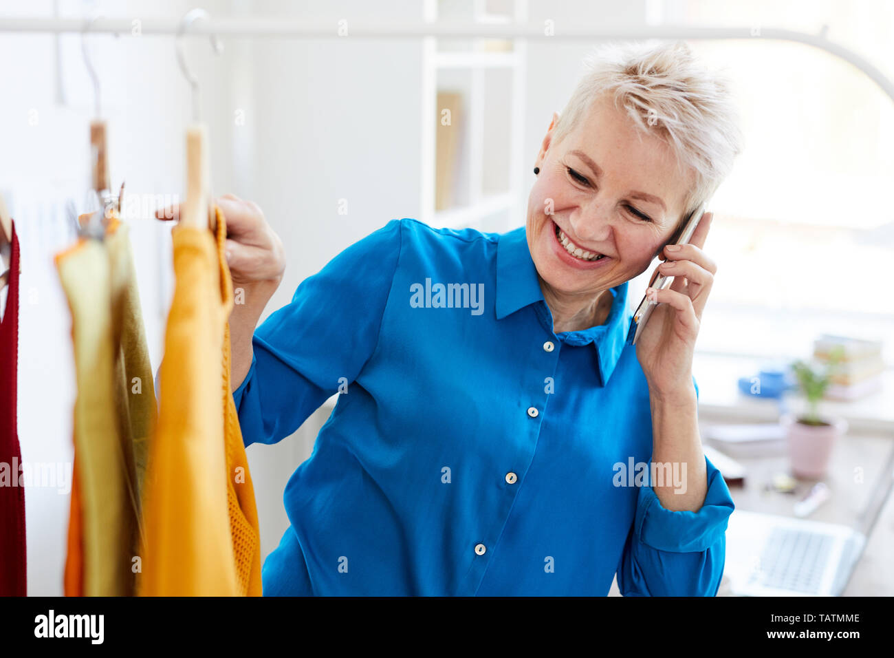Cheerful blonde woman with smartphone consulting with her friend or daughter while looking for new casualwear in boutique - Stock Image