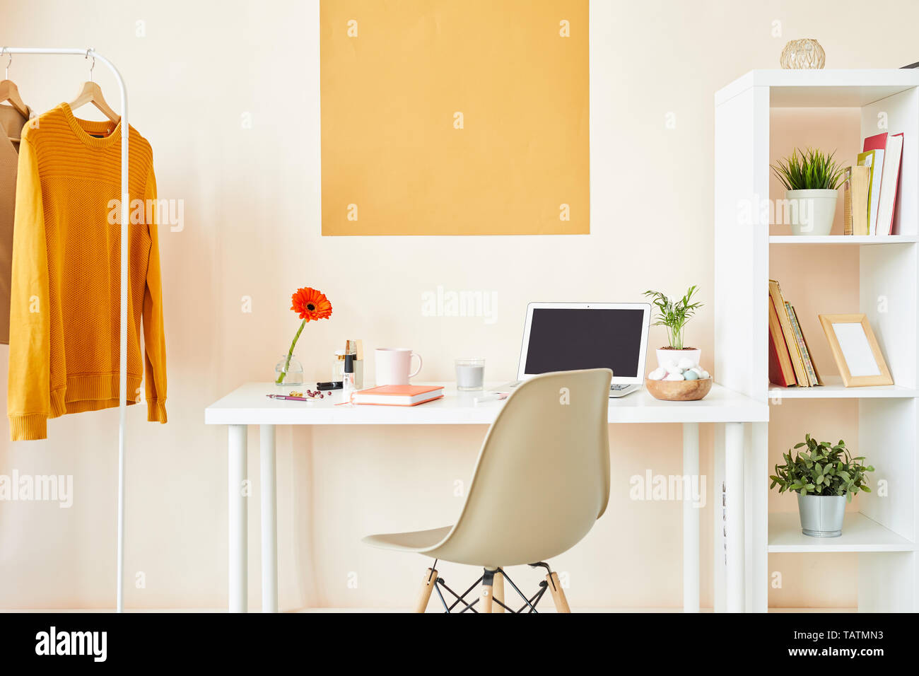 Workplace of creative employee or designer with desk by wall, white chair, furniture with stuff and casualwear on hangers - Stock Image