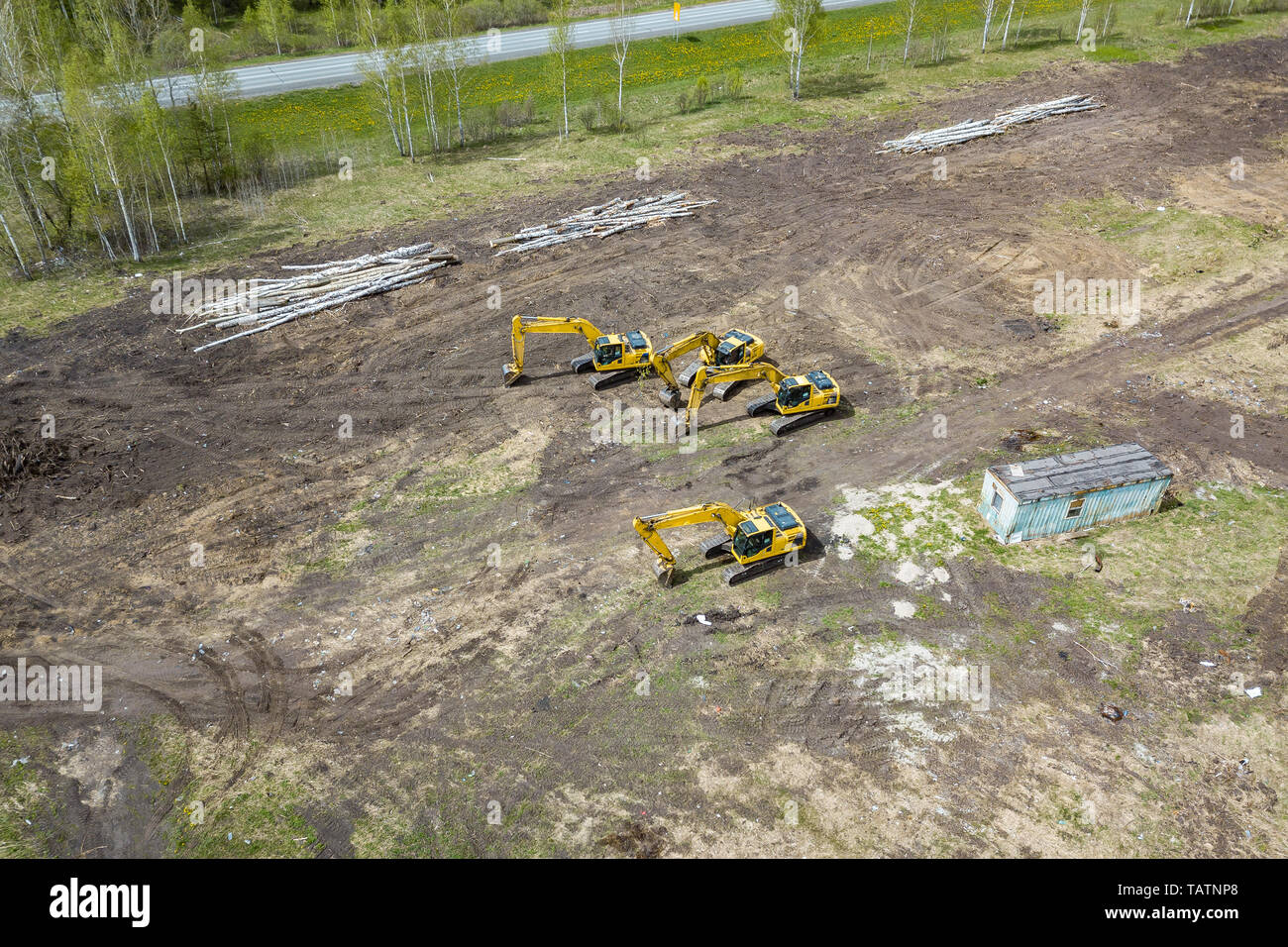 Aerial side view of four yellow crawler excavators standing on ground near the construction site and waiting for the working day to start digging the  - Stock Image