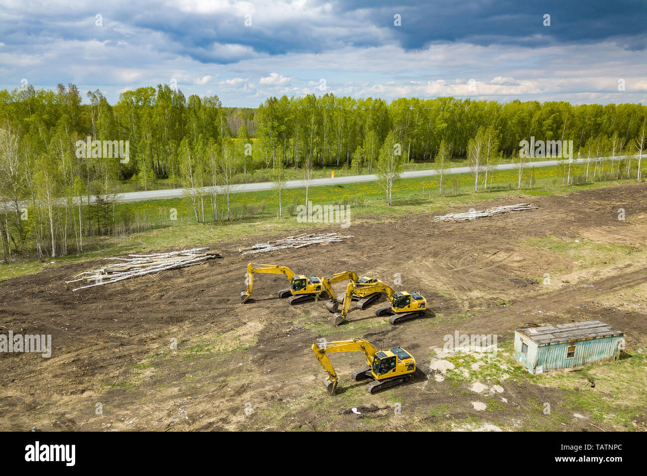 Aerial top view of four yellow crawler excavators standing on ground near the construction site and waiting to start digging the ground near the road  - Stock Image