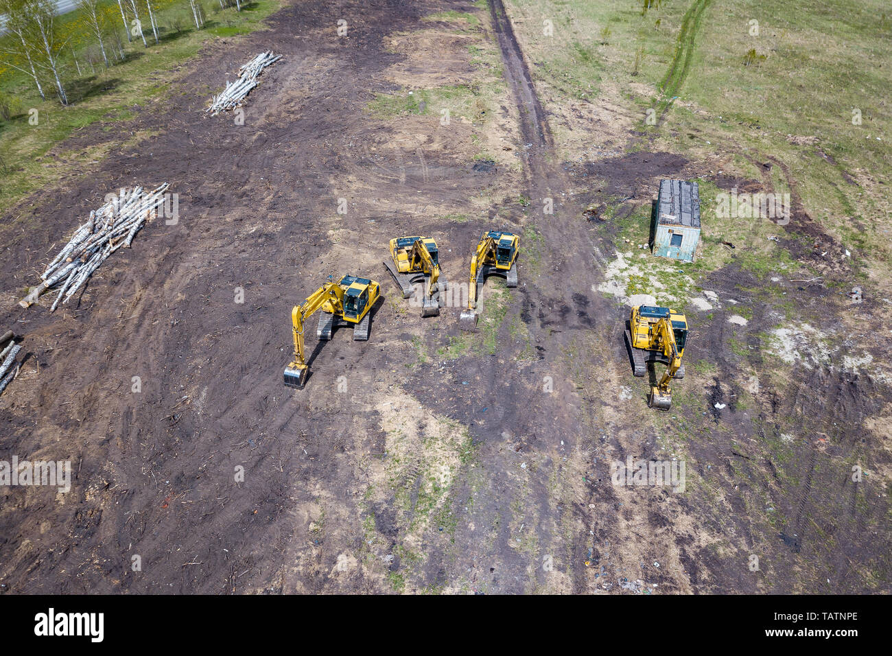 Aerial top view of four yellow crawler excavators standing on ground near the construction site and waiting for the working day to start digging the g - Stock Image