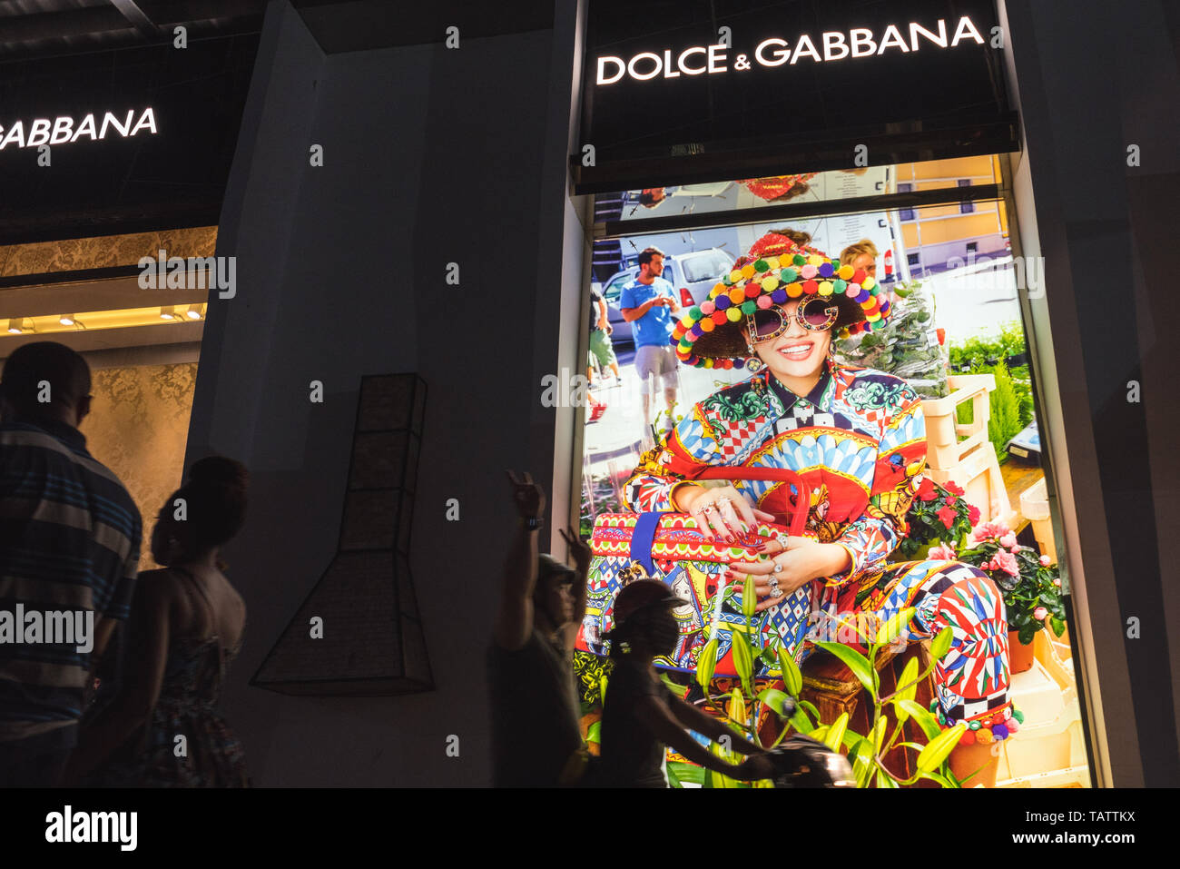 Ho Chi Minh City, Vietnam - April 23, 2019: Dolce & Gabbana shop's exterior with people passing by in the night street, on a motorbike and afoot. - Stock Image