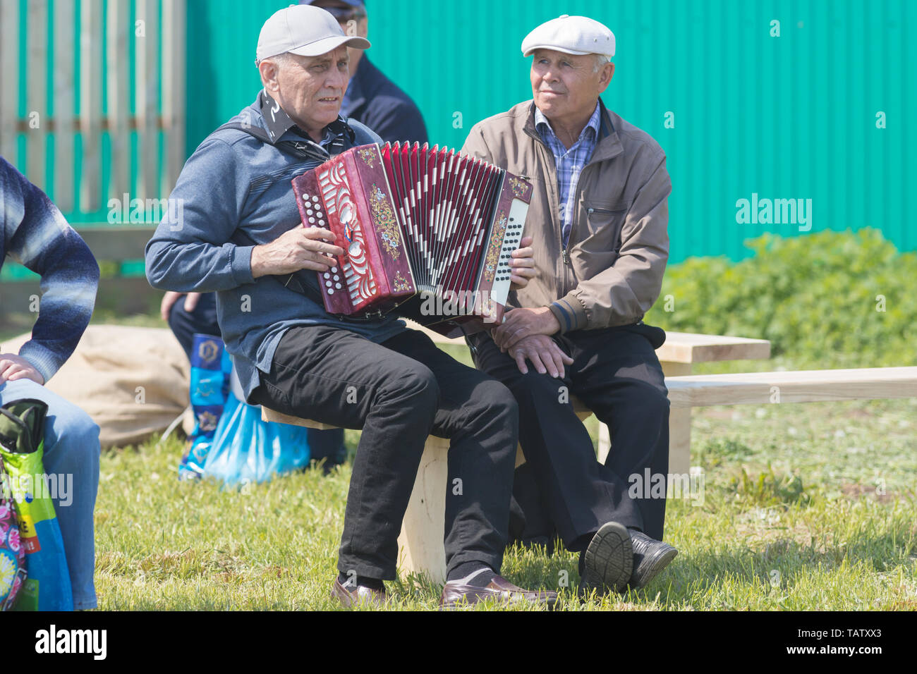 RUSSIA, Nikolskoe village, Republic of Tatarstan 25-05-2019: A group of old men sitting on the bench. One of them playing accordion. Mid shot Stock Photo