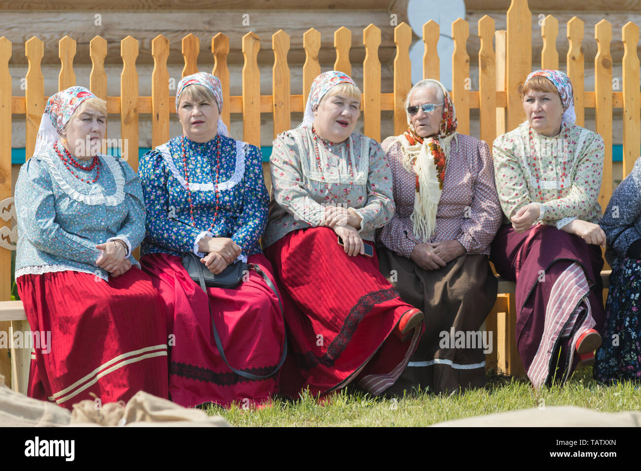 RUSSIA, Nikolskoe village, Republic of Tatarstan 25-05-2019: A group of old women sitting on the bench and talking. Mid shot Stock Photo