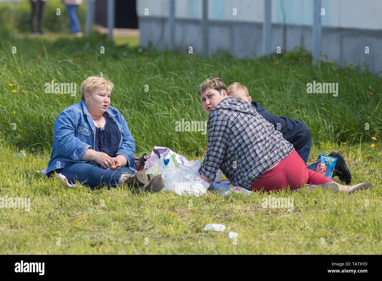 RUSSIA, Nikolskoe village, Republic of Tatarstan 25-05-2019: Three mature overweight women sitting on the blanket in a village and having a picnic. An Stock Photo