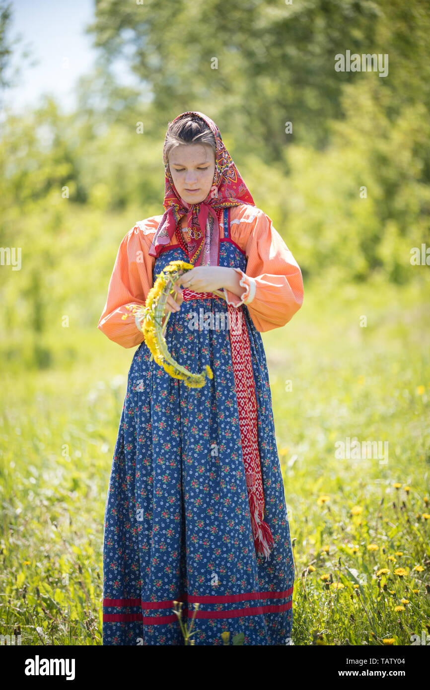 RUSSIA, Nikolskoe village, Republic of Tatarstan 25-05-2019: A young woman in traditional russian clothes making a wreath. Mid shot Stock Photo