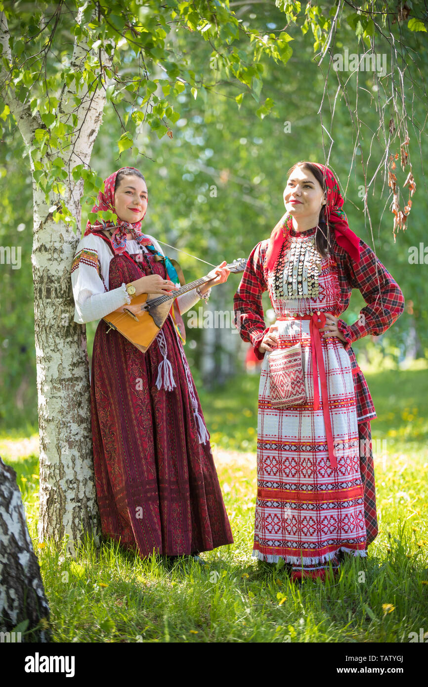 Two smiling woman in traditional russian clothes standing in the forest. One of them holding balalaika. Vertical shot Stock Photo