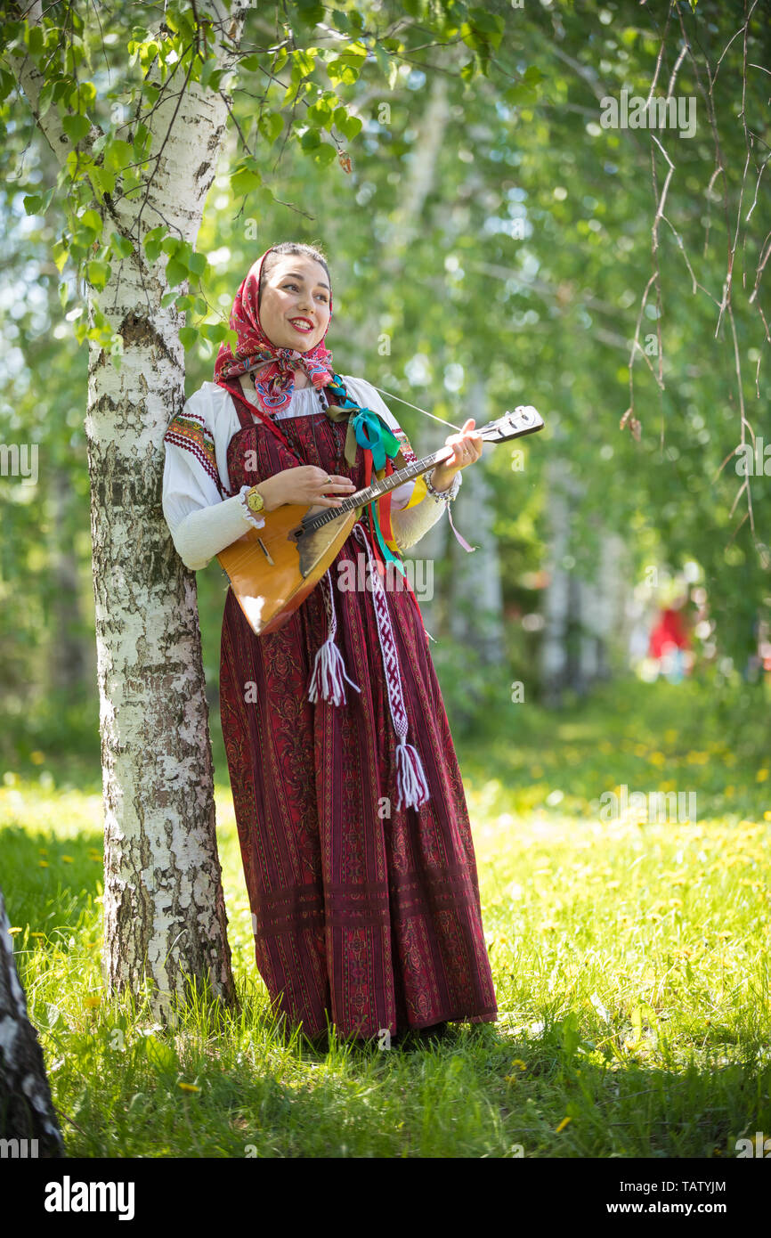 Young romantic woman in traditional russian clothes standing in the forest and holding balalaika, vertical Stock Photo