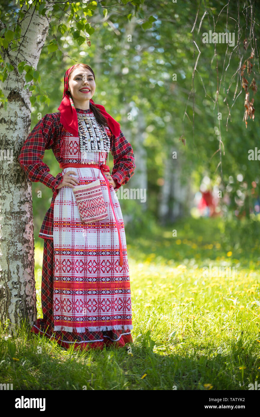 Young woman in traditional russian clothes standing in the forest and holds hands on a waist - vertical shot Stock Photo