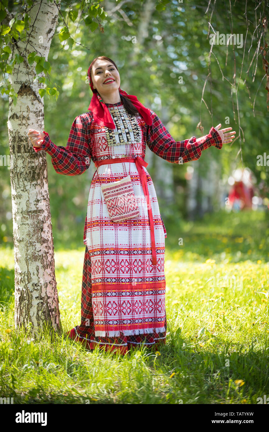 Young woman in traditional russian clothes standing in the forest and throws up her hands - vertical shot Stock Photo
