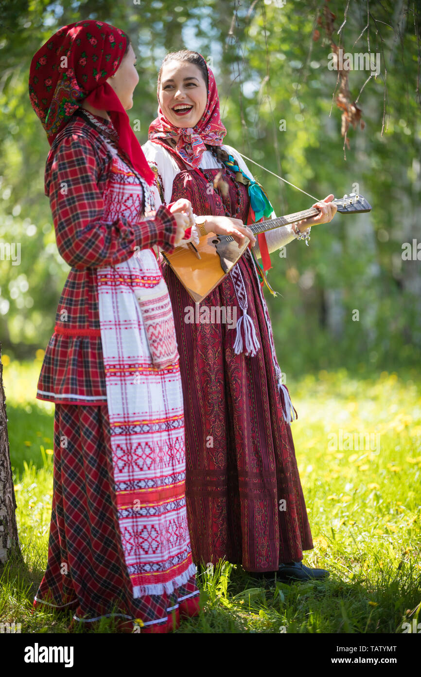 Two young woman in traditional russian clothes standing in the forest and look at each other. One of them playing balalaika and sing - vertical shot Stock Photo