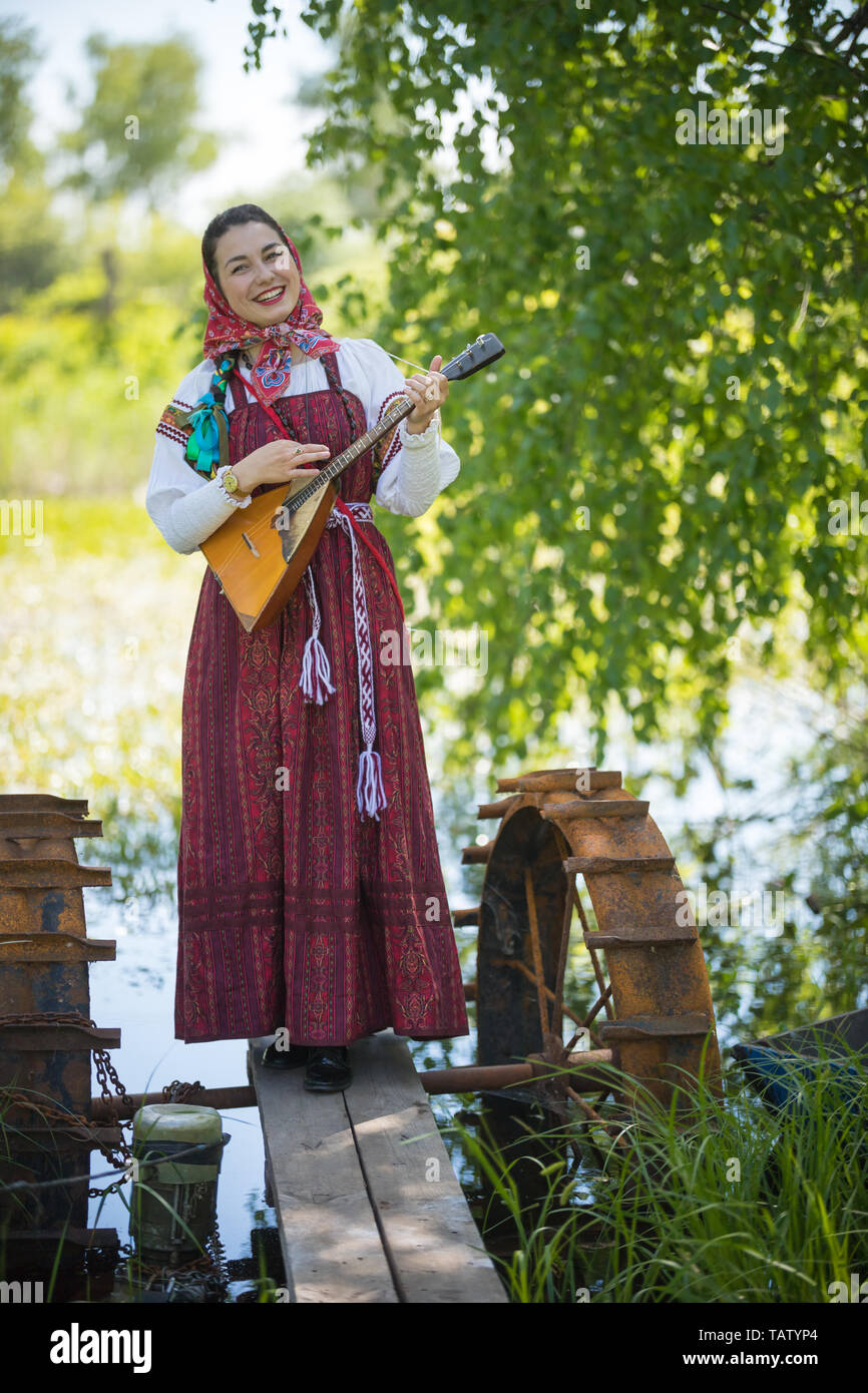 Young smiling woman in traditional russian clothes stands on a small bridge near the lake, and playing balalaika, vertical shot Stock Photo