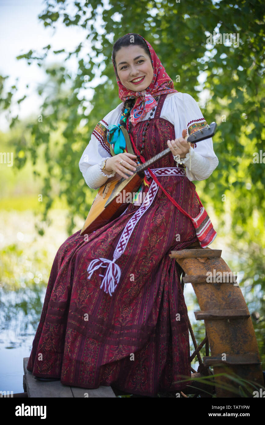 Young romantic woman in traditional russian clothes sits on the small pier near the lake, and play music on balalaika - vertical shot Stock Photo