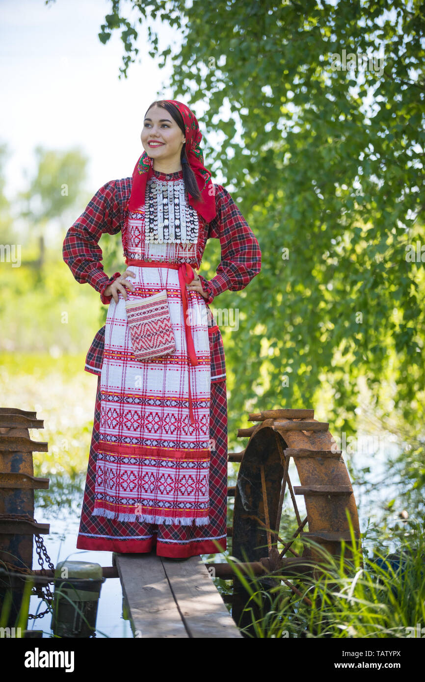 Young woman in scarf and traditional russian clothes stands on a small pier near the lake, and holds hands on a waist, vertical view Stock Photo