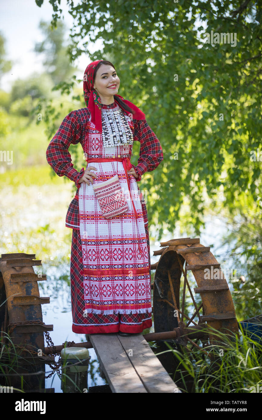 Young woman in scarf and traditional russian clothes stands on a small pier near the lake and holds hands on a waist looking left vertical view. Stock Photo