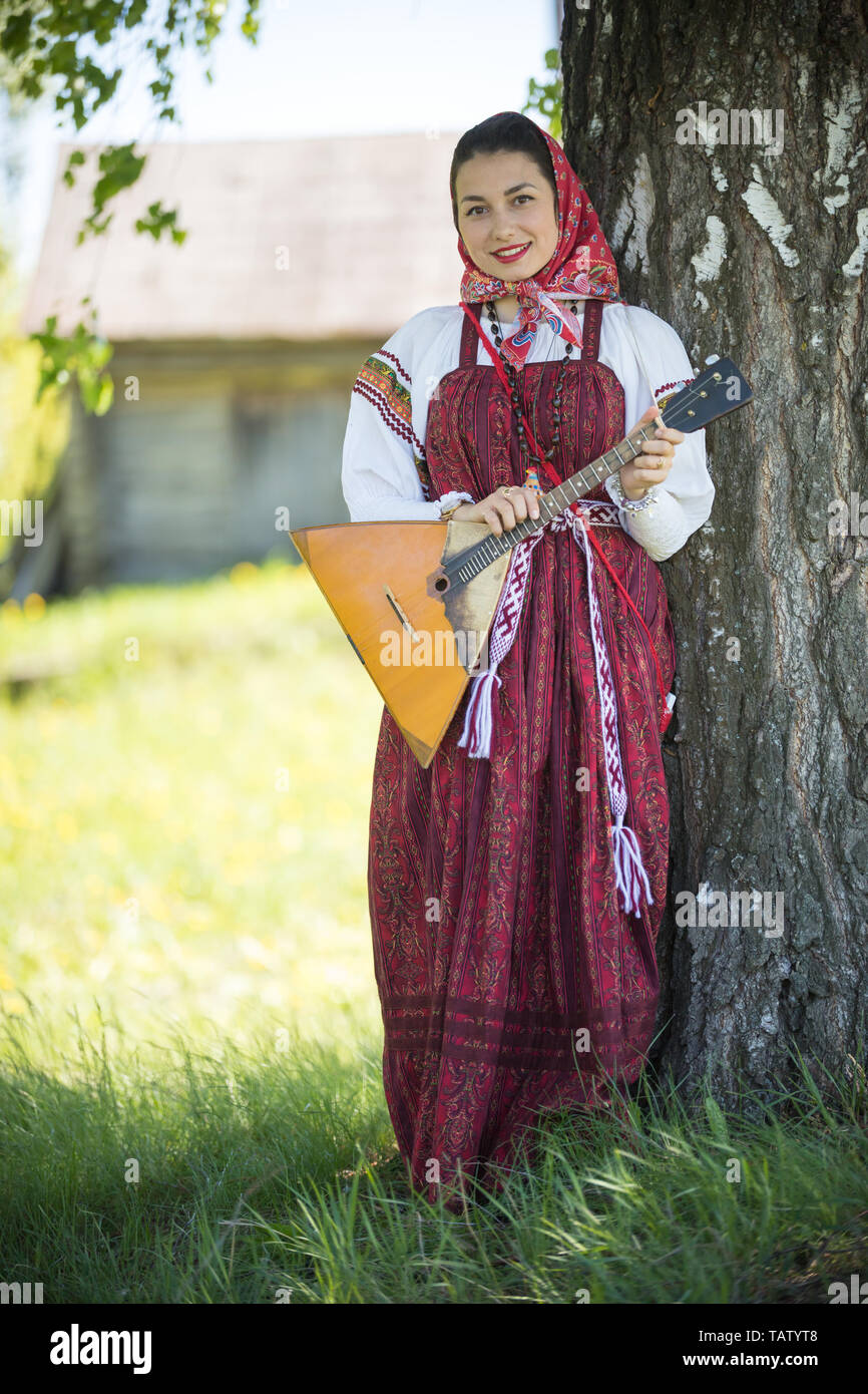 Young attractive woman in traditional russian clothes standing under a tree with the balalaika and posing for a photo - vertical shot Stock Photo