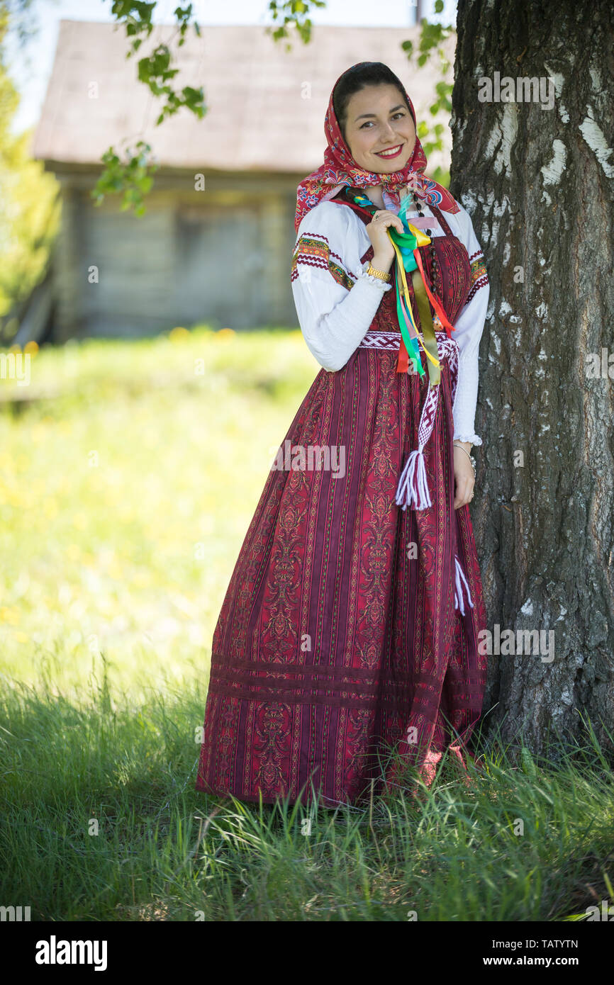 Young woman in traditional russian clothes standing under a tree and holding her pigtail - vertical shot Stock Photo