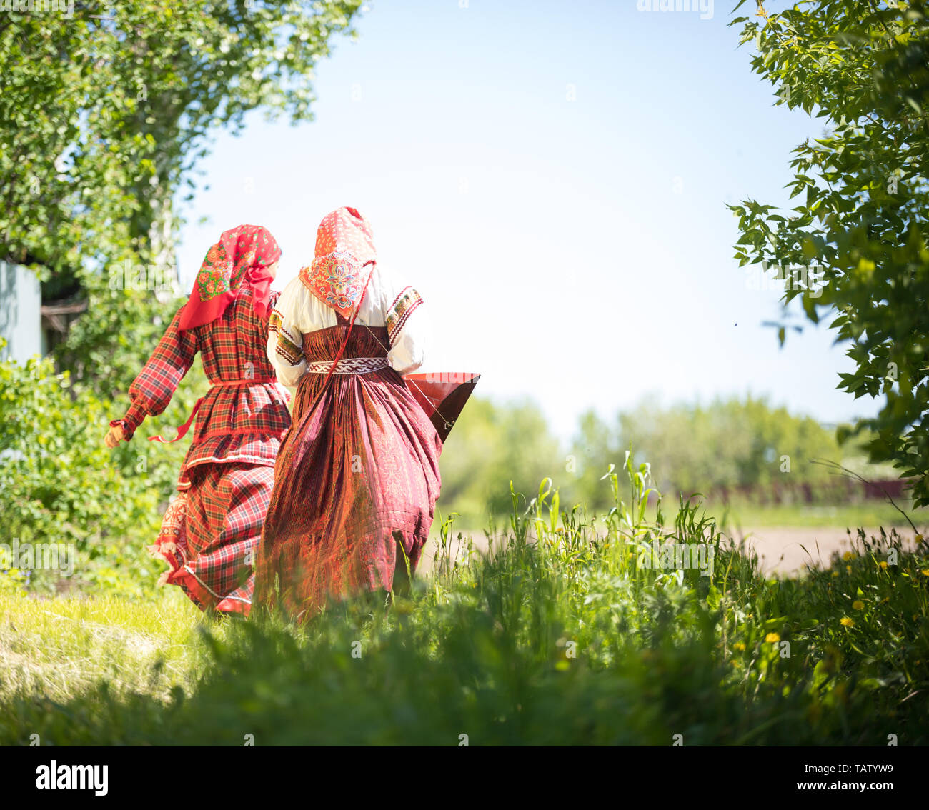 Two young women in traditional russian clothes stand in the field between the trees - holding hadns backview Stock Photo