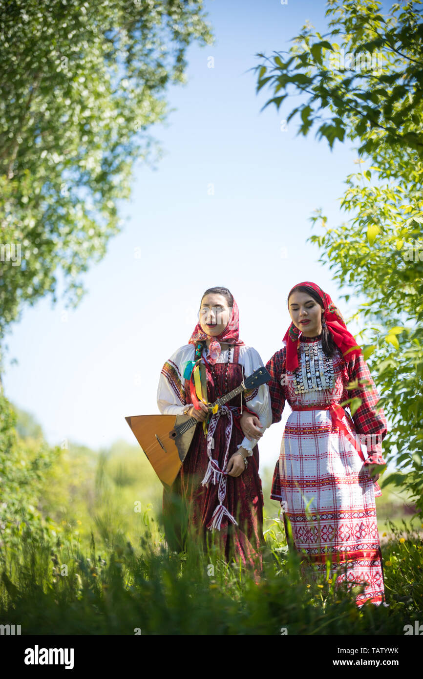 Two young women in traditional russian clothes stand in the field between the trees and singing - vertical shot Stock Photo