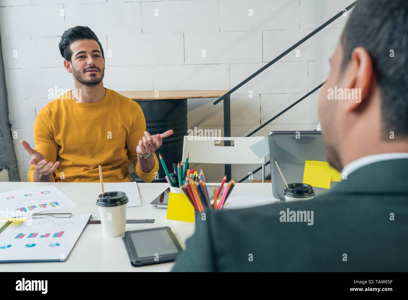 A young man is interviewed for a job. Guy's talking to his boss in the office. Business communication. Stock Photo