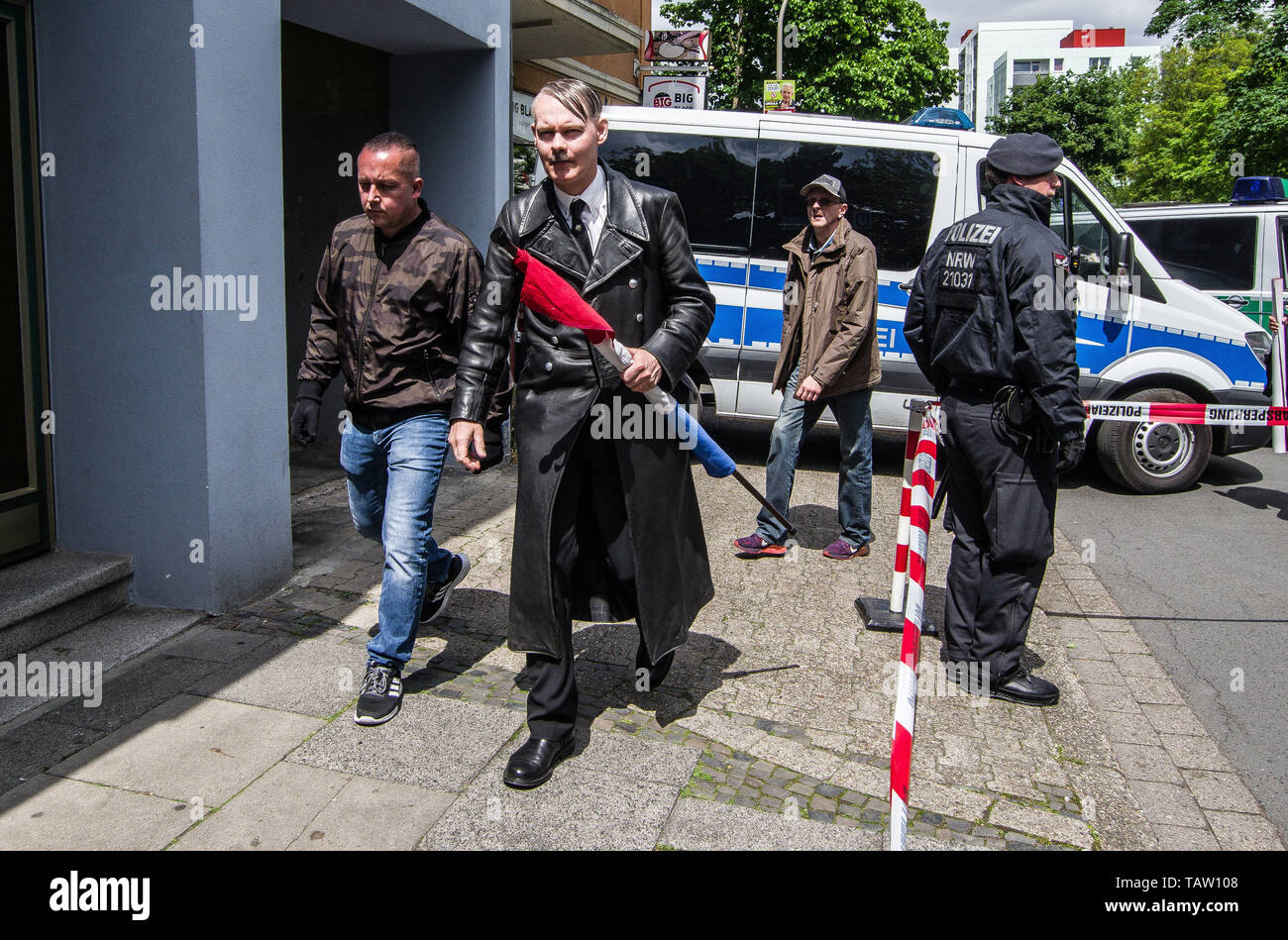 Dortmund, Nordrhein Westfalen, Germany. 25th May, 2019. A neonazi from The Netherlands has fashioned himself into the appearance of Adolph Hitler. On his tie is a pin of the Edelweiss flower, which was used by the SS and is still in use by the Gebirgsjaeger today. Prior to the European Elections, the neonazi party Die Rechte (The Right) organized a rally in the German city of Dortmund to promote their candidate, the incarcerated Holocaust denier Ursula Haverbeck. The demonstration and march were organized by prominent local political figure and neonazi activist Michael Brueck (Michael Brück Stock Photo
