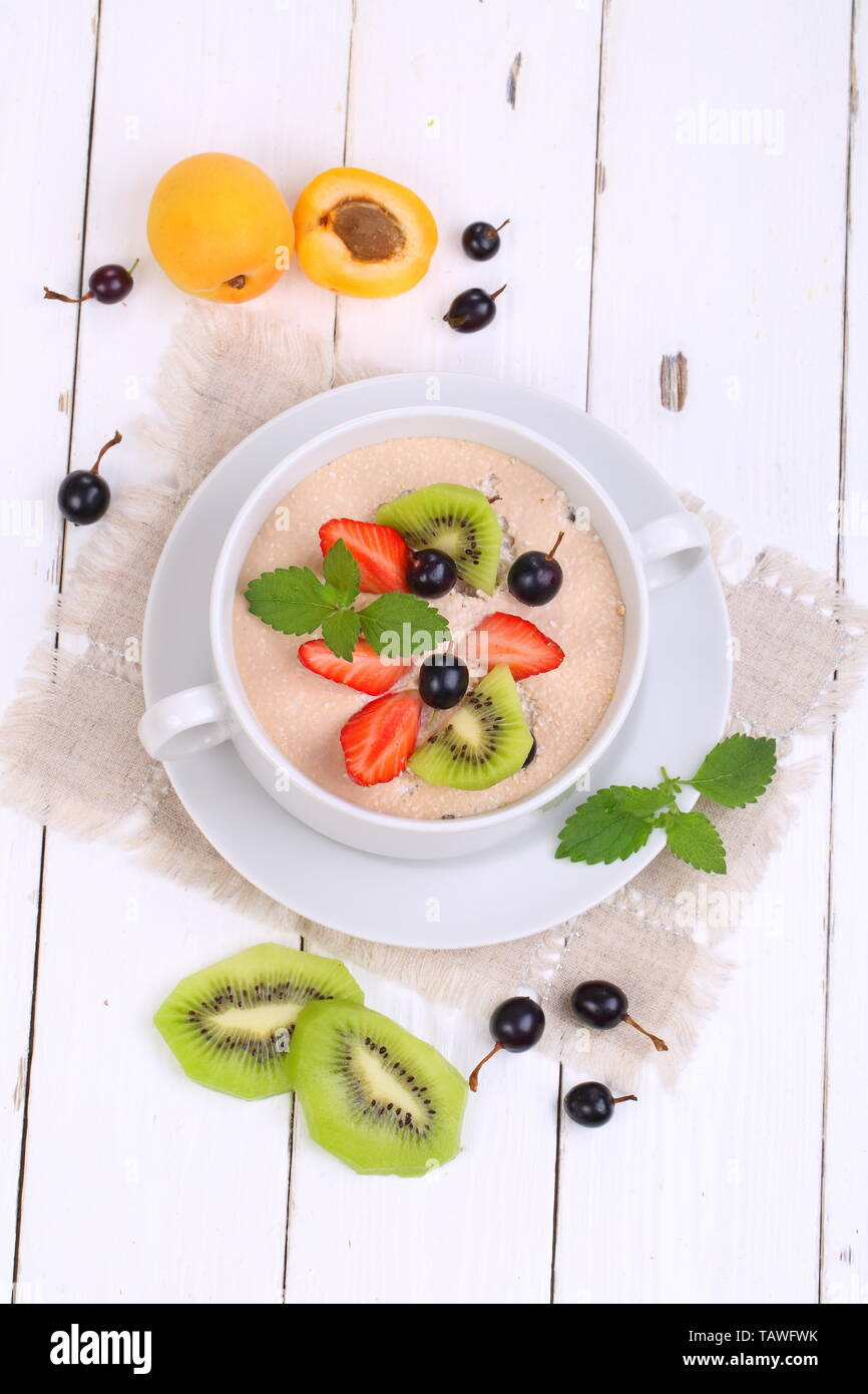 Oatmeal with strawberries, black currant, mint on a white wooden background Stock Photo