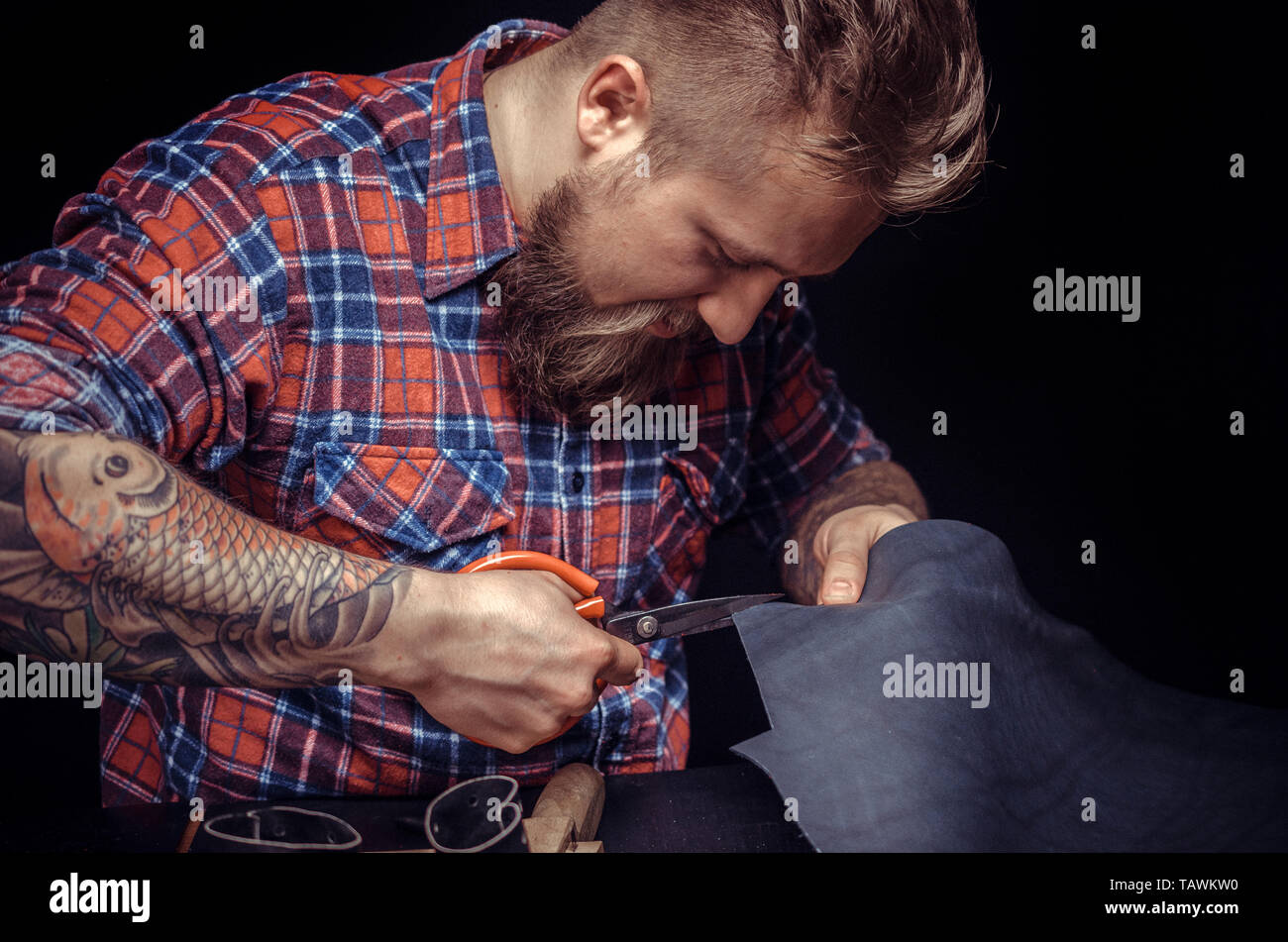 Craftsman working with leather making quality products at the leather shop. - Stock Image