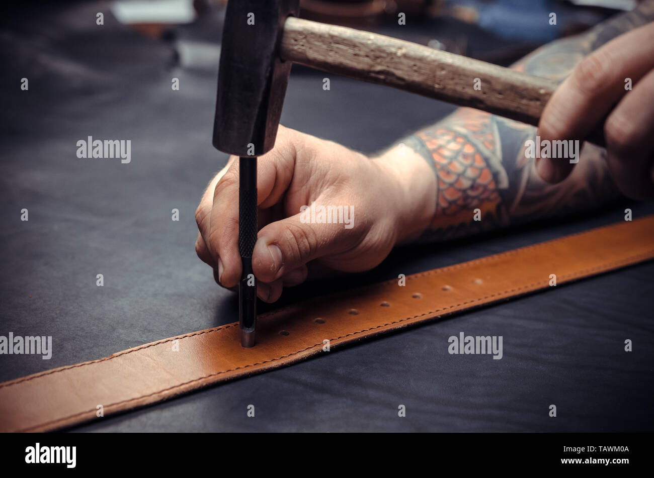 Leather workman manufacturing new leather product in leather shop. - Stock Image
