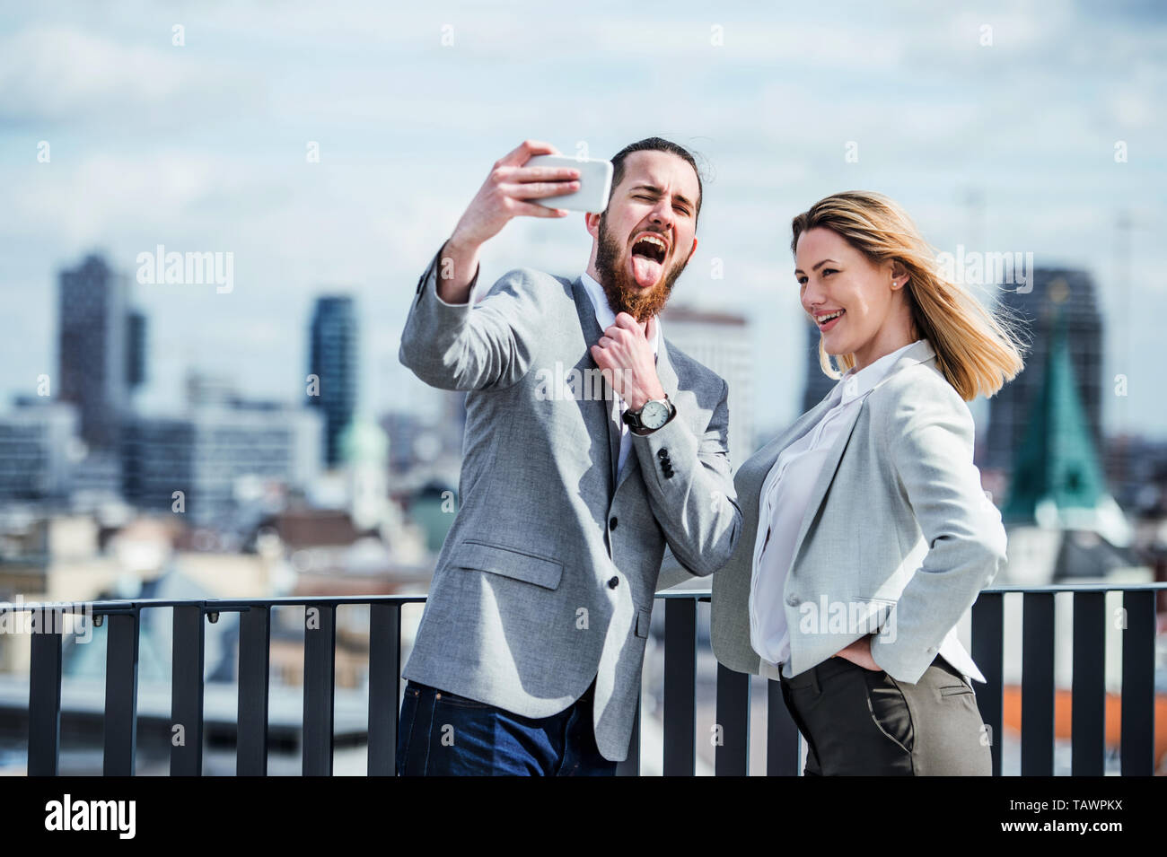Two young business people with smartphone standing on a terrace, taking selfie. - Stock Image