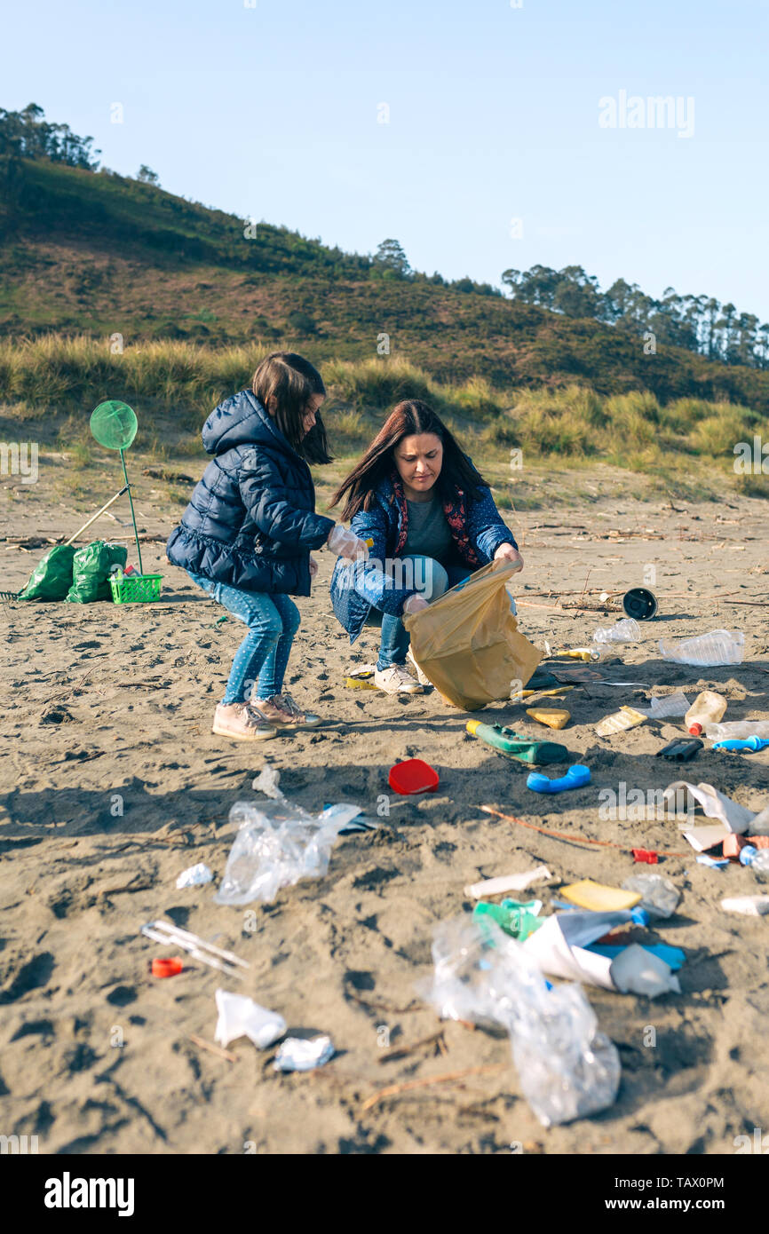 Female volunteers cleaning the beach - Stock Image