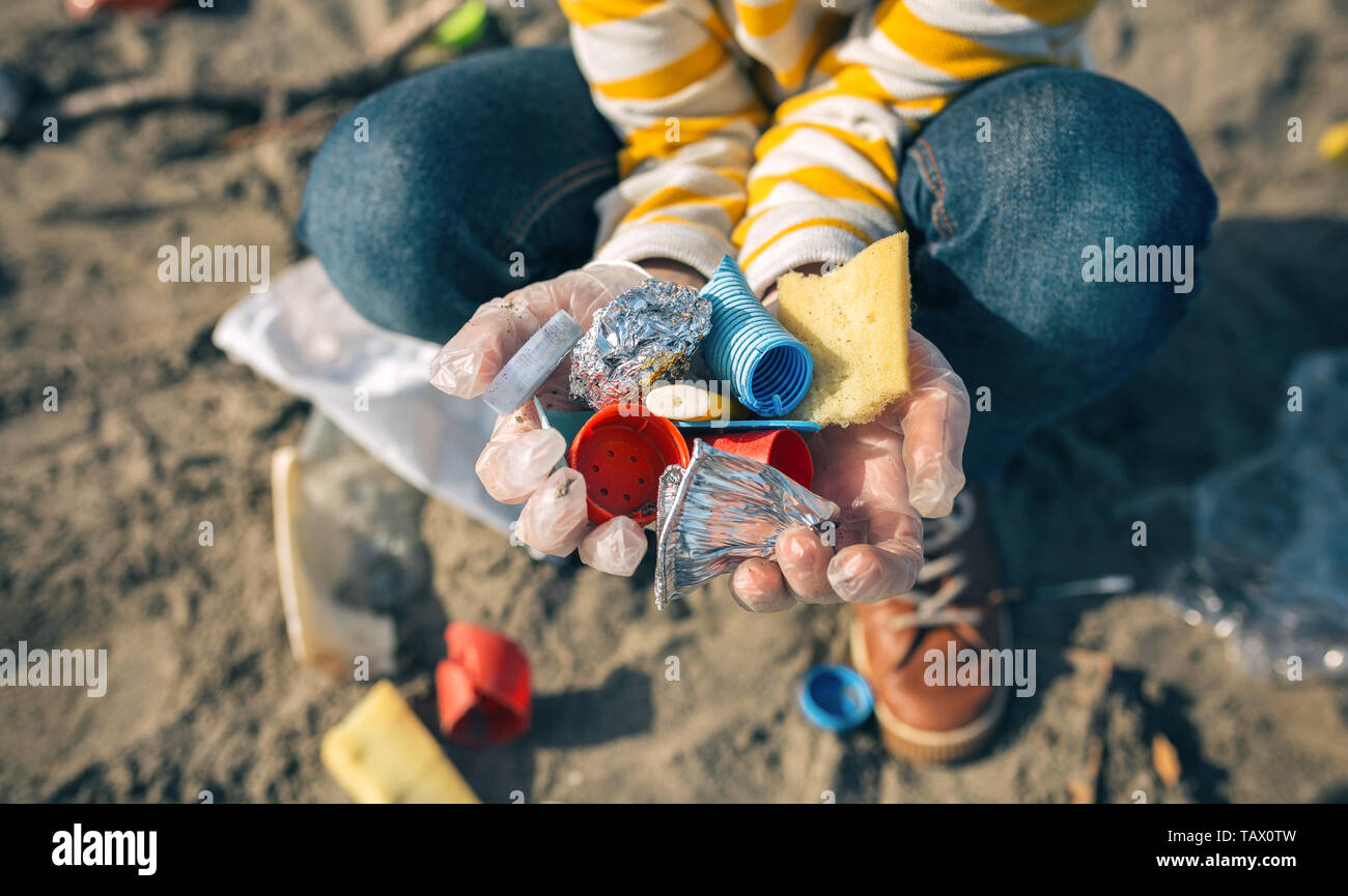 Child hands with garbage from the beach - Stock Image