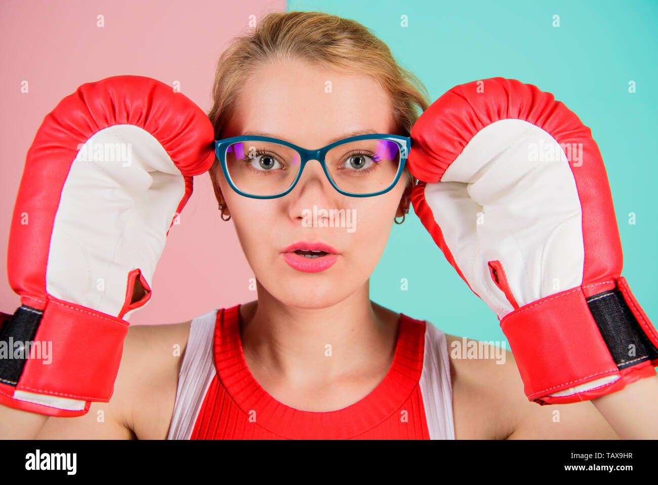 Strong mentally and physically. Smart and strong. Woman boxing gloves adjust eyeglasses. Win with strength or intellect. Strong intellect victory pledge. Know how defend myself. Confident her power. - Stock Image