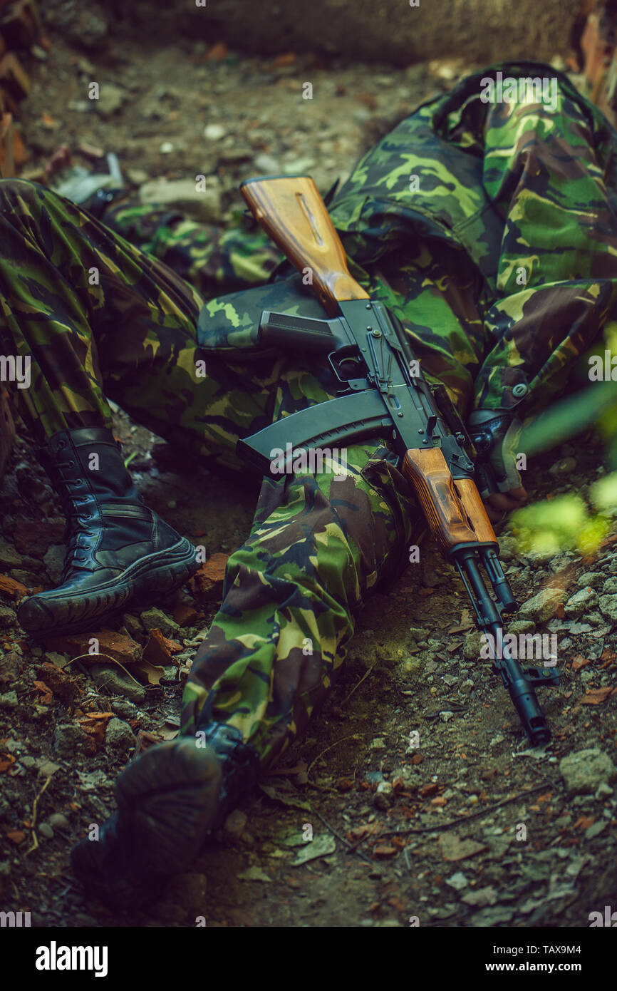 Dead body of killed soldier in war dressed in military ammunition laying on ground with rifle outdoor - Stock Image