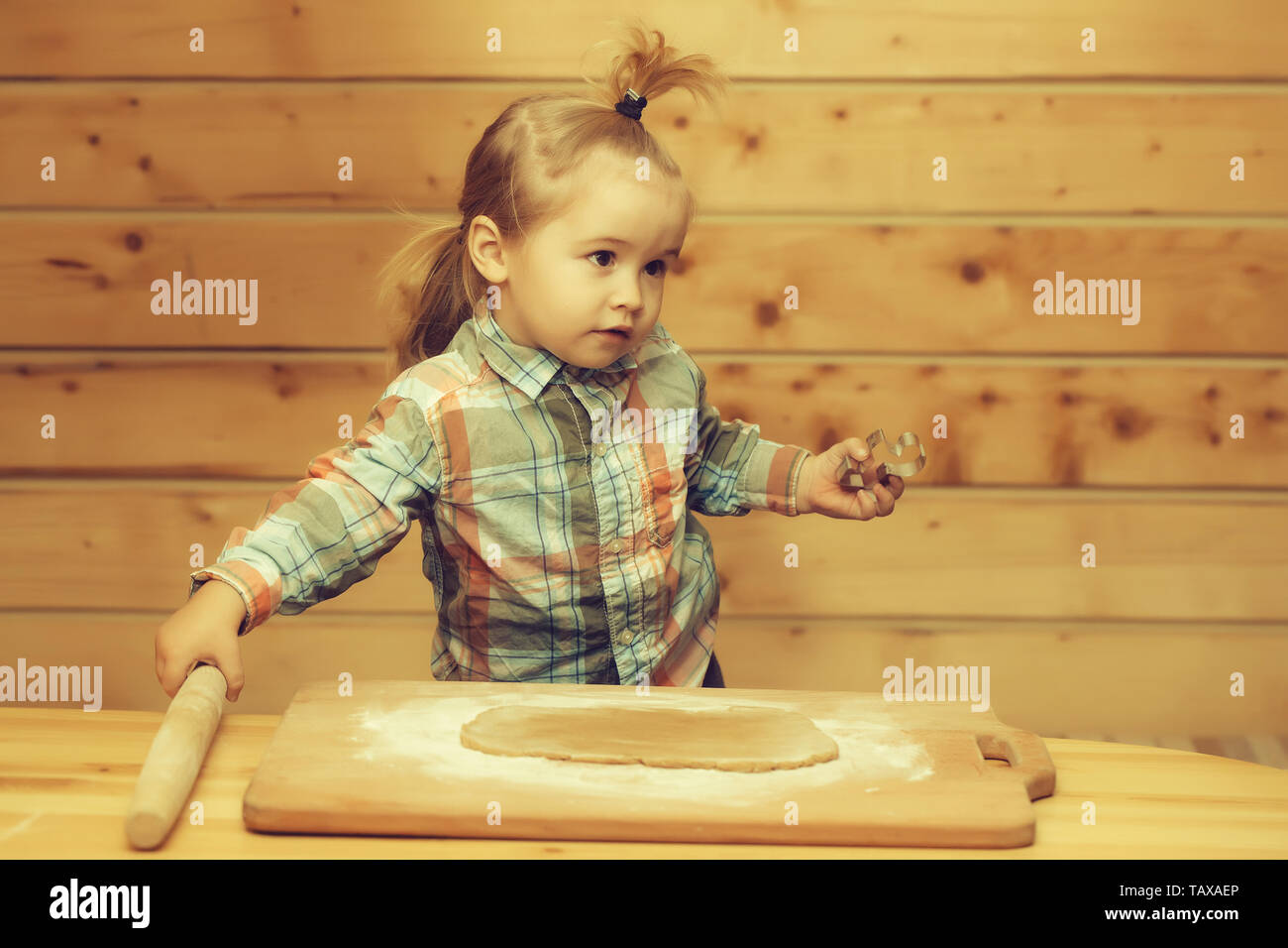 5b49c90e3 adorable small child chef or cute baby boy in fashionable chekered shirt  cooking on board flour