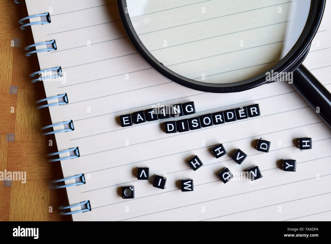 Eating Disorder on wooden block and magnifying glass. Motivation concept - Stock Image