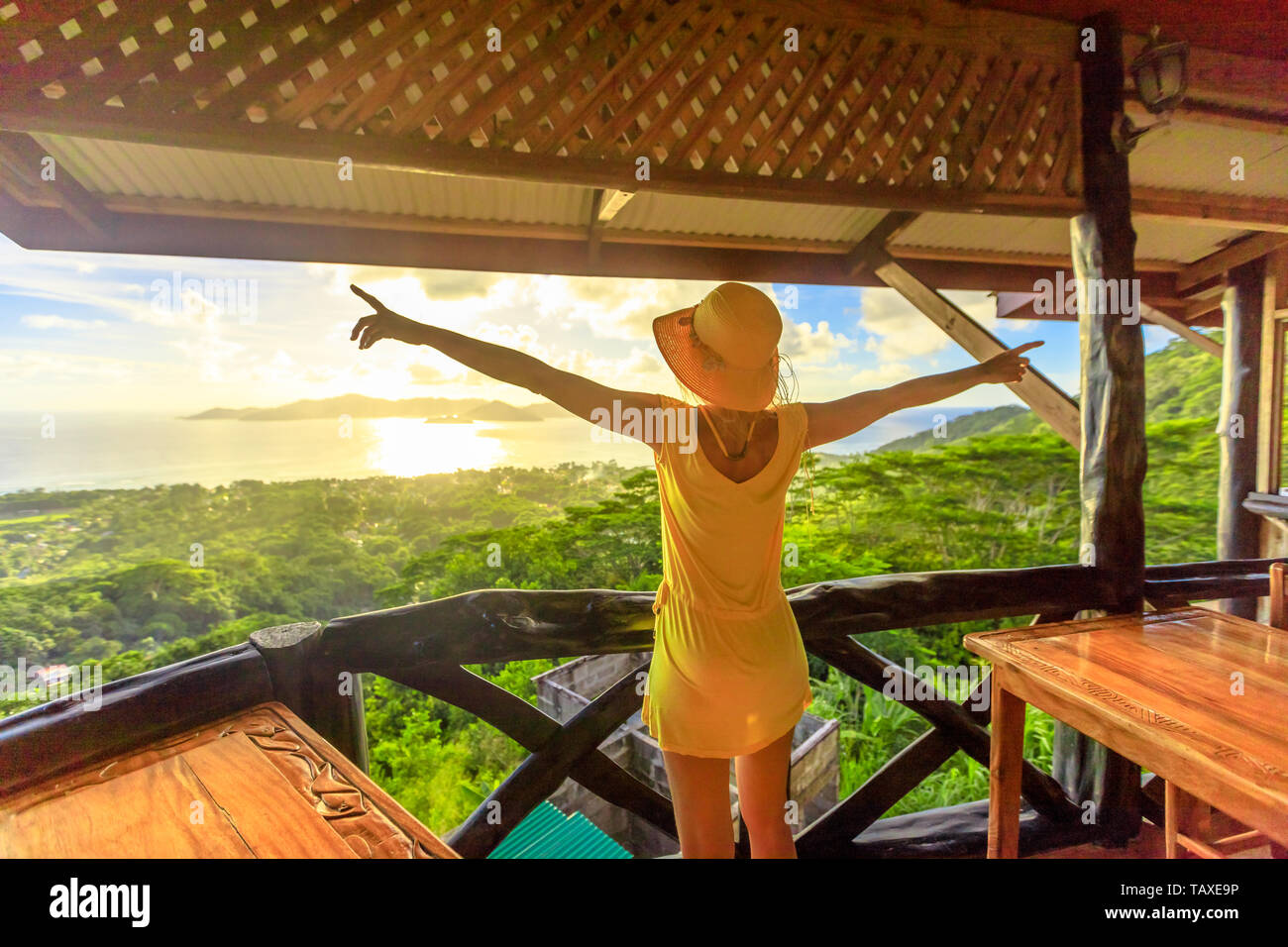 Carefree lifestyle female enjoying spectacular views of Seychelles and Indian Ocean at sunset light. Elegant tourist woman in yellow dress looking at - Stock Image