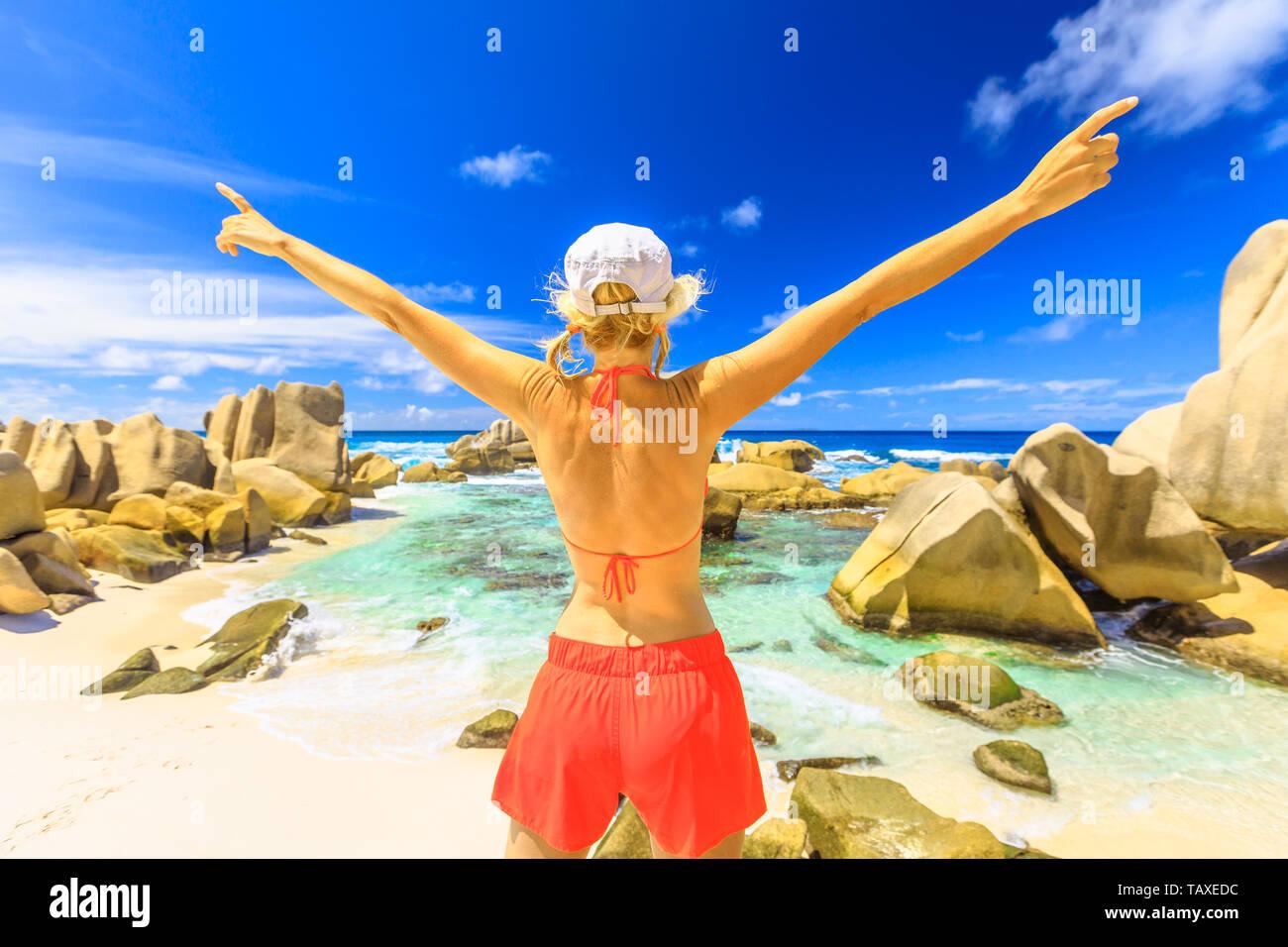 Aerial view of swimming natural pool, La Digue, Anse Marron. Tourist girl in orange bikini with raised arms enjoying on a granite boulder at Anse - Stock Image