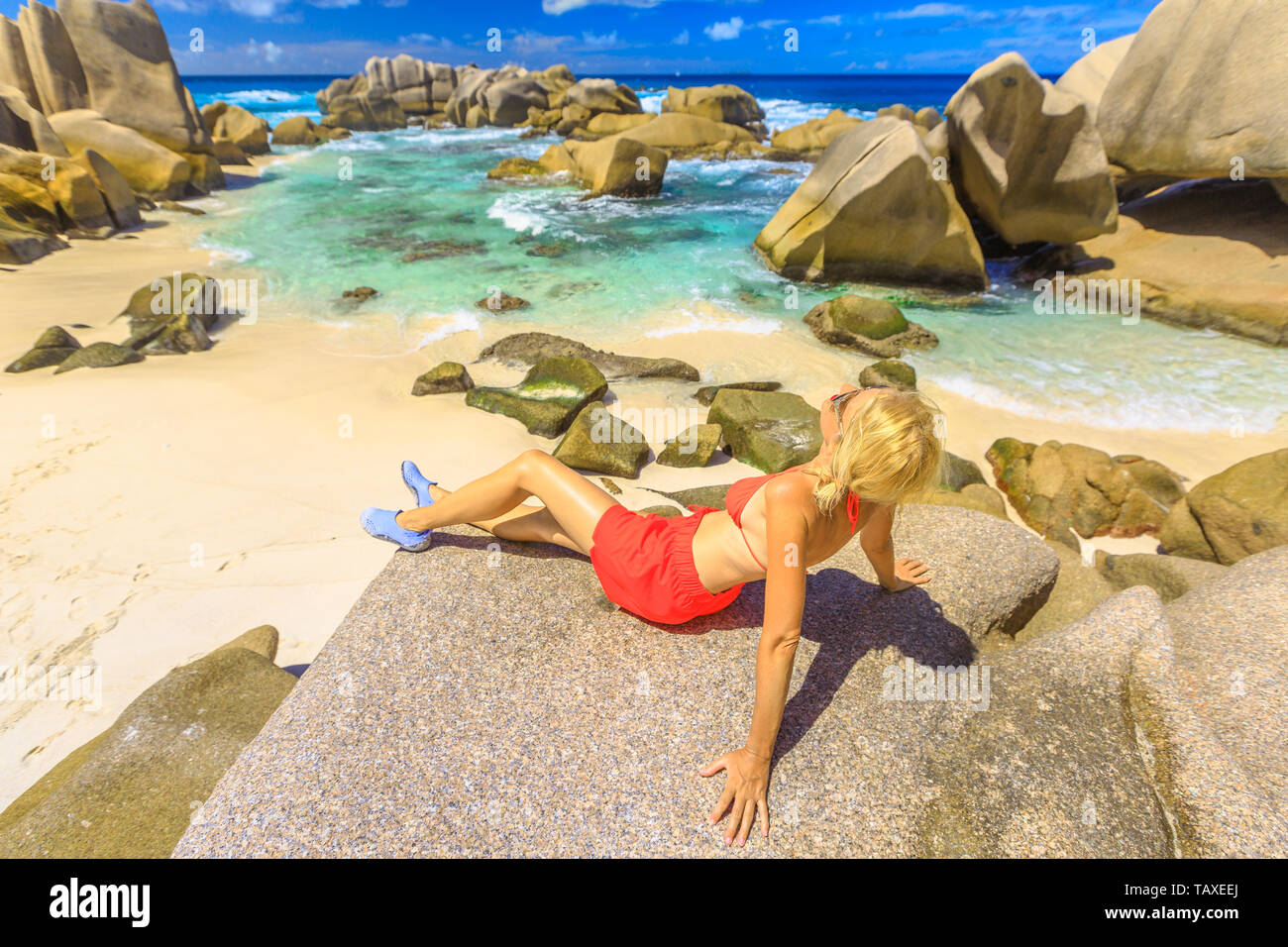 Tourist woman in orange bikini, sunbathing on a boulder granite at Anse Marron protected by huge rock formations. Aerial view of natural pool, La - Stock Image