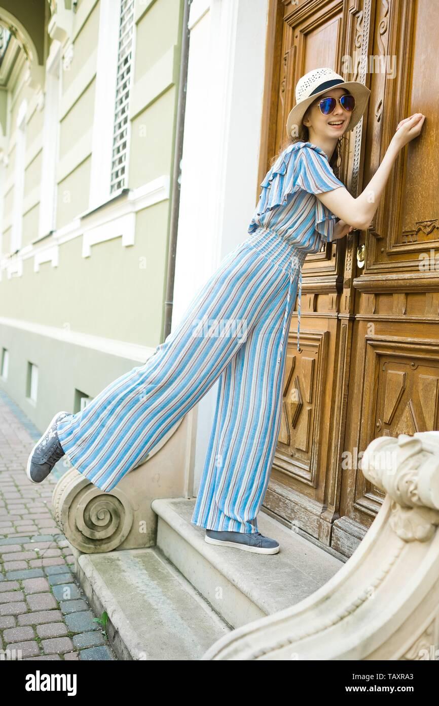 Teenaged girl in jumpsuit dress is knocking on vintage wooden door of old building - Stock Image