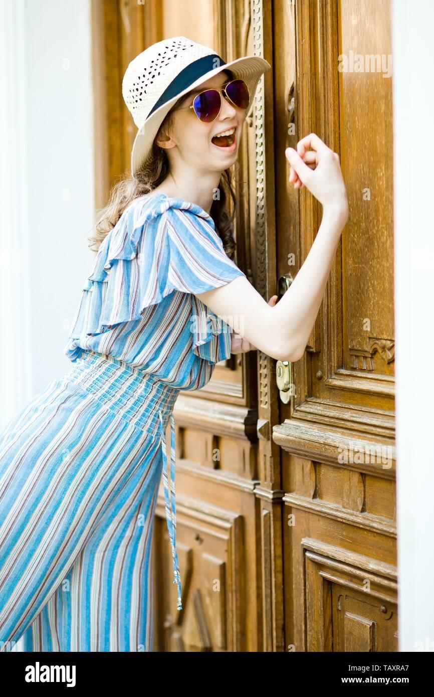 Young joyful girl in jumpsuit dress is knocking on vintage wooden door - Stock Image