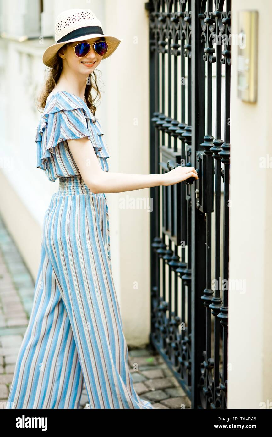 Attractive girl in jumpsuit dress is opening black forged gates, side view - Stock Image