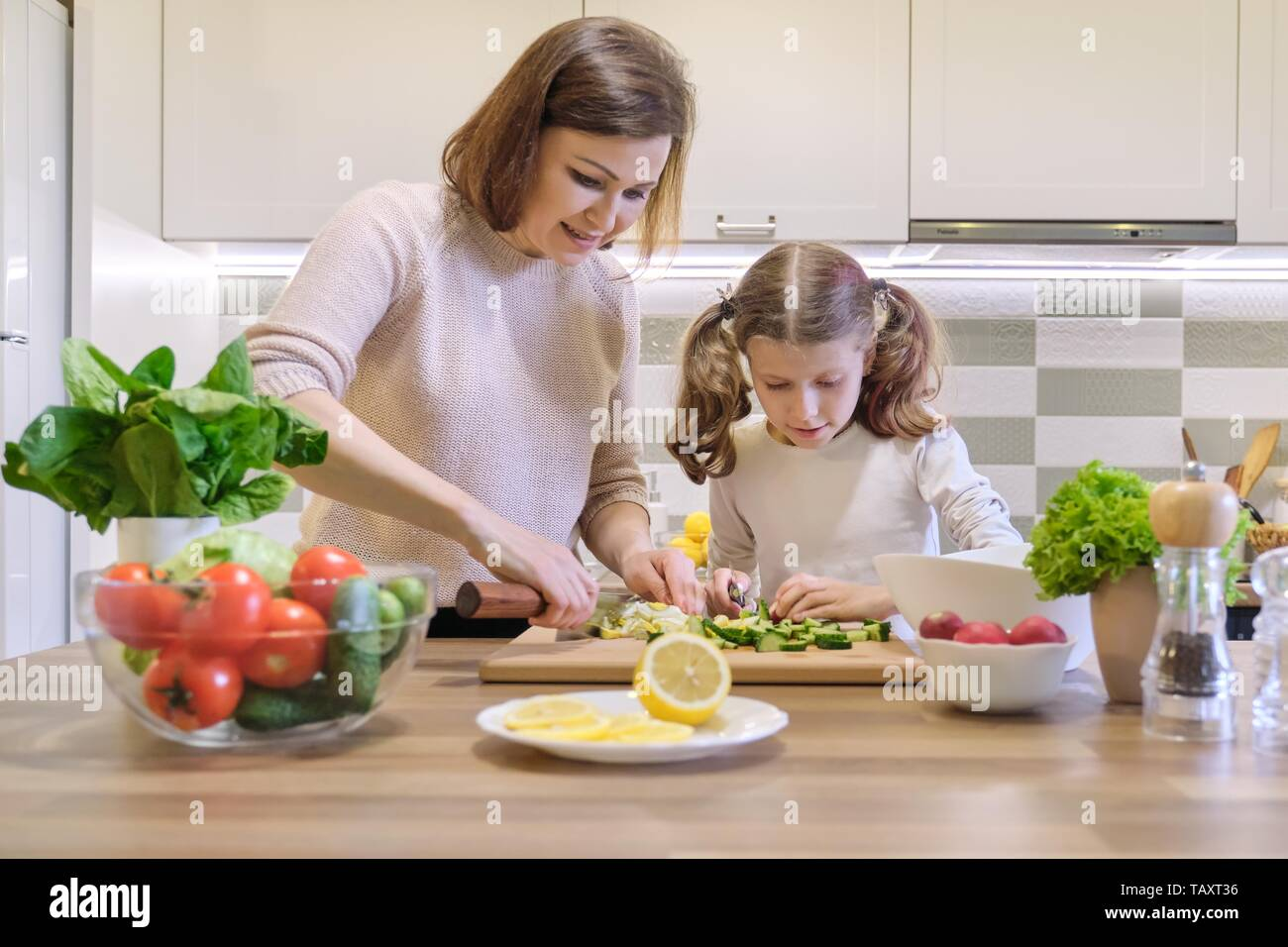 Mother and child cooking together at home in kitchen
