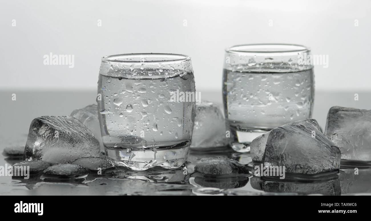 Shots of vodka in glasses. White background with ice cubes. Alcohol drink vodka tequila - Stock Image